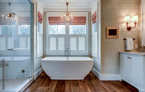 Photo High end bathroom with large white bathtub and shiplap siding.