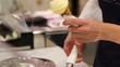 Vendor are serving vanilla ice cream. Close up hand woman. Selective focus. Food concept.
