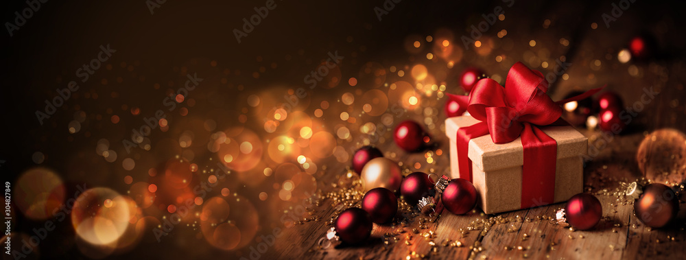 Obraz Abstract Christmas Banner  -  Gift box with red bow and baubles on wood  -  Magic dark golden bokeh lights background fototapeta, plakat