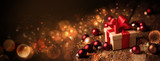 Abstract Christmas Banner  -  Gift box with red bow and baubles on wood  -  Magic dark golden bokeh lights background