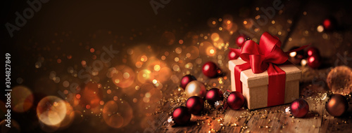 Abstract Christmas Banner  -  Gift box with red bow and baubles on wood  -  Magic dark golden bokeh lights background - 304827849