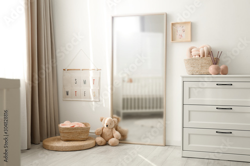 Beautiful nursery interior with white chest of drawers