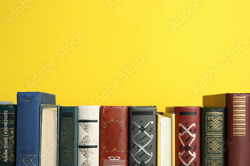 Fotomural  Collection of old books on yellow background, space for text