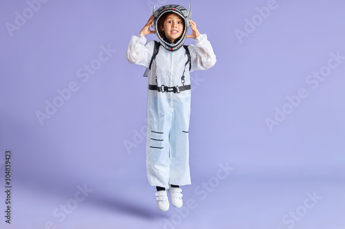 Fotomural Portrait of child boy in protective white suit while jumping up isolated over pu