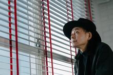 窓際で帽子を被ったシニア男性のポートレート