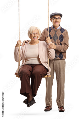 Fototapety, obrazy: Senior woman sitting on a swing with her husband standing beside her