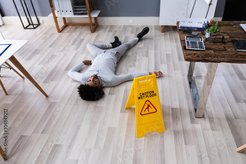 Fotografie, Tablou  Man Falling On Wet Floor In Front Of Caution Sign