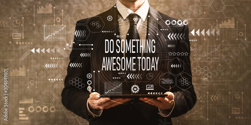 Photo Do something awesome today with businessman holding a tablet computer on a dark