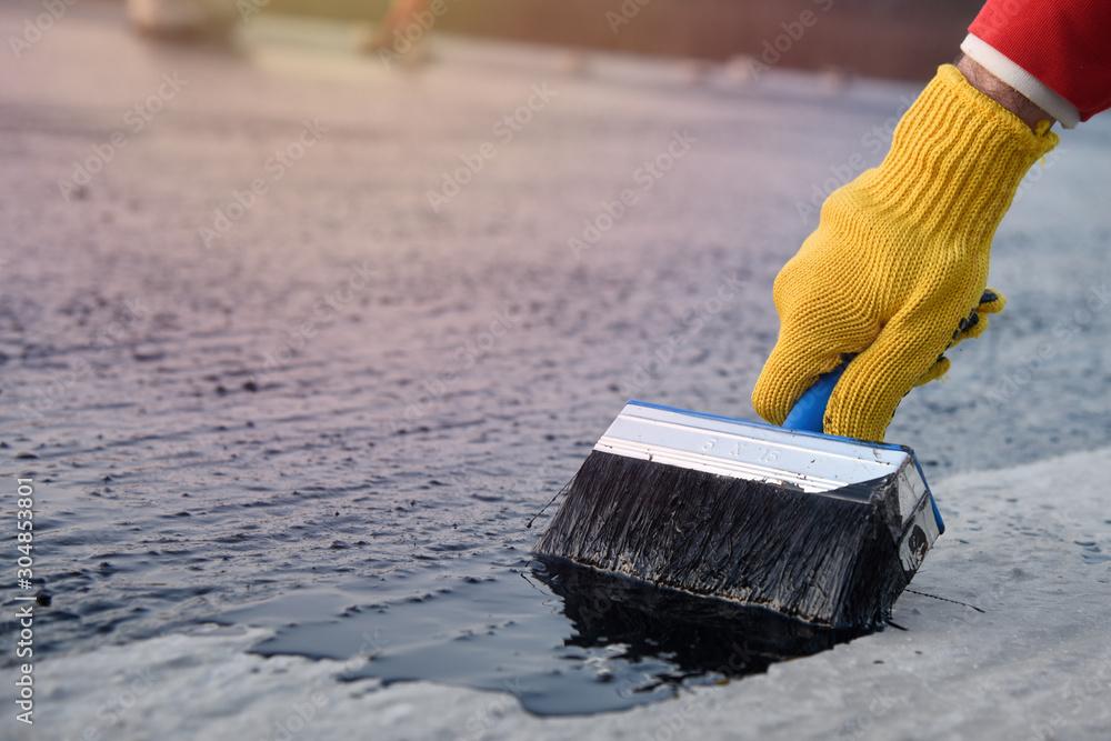 Fototapeta Worker applies bitumen mastic on the foundation