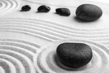 Black Stones On Sand With Patt...