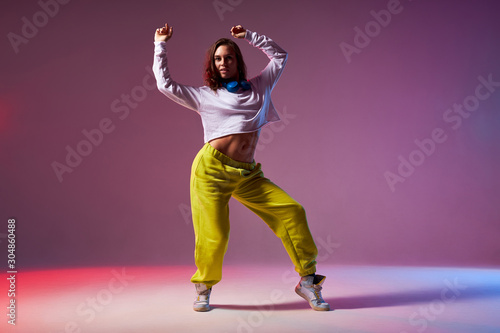 Fotografija Athletic modern style dancer performing dance element, standing on stage of scho