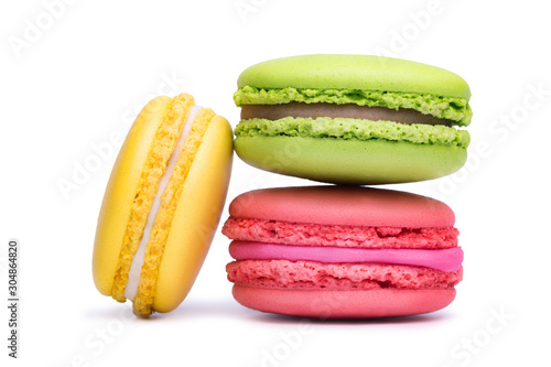 Fototapeta Yellow, pink and green macaron cookies isolated on white background