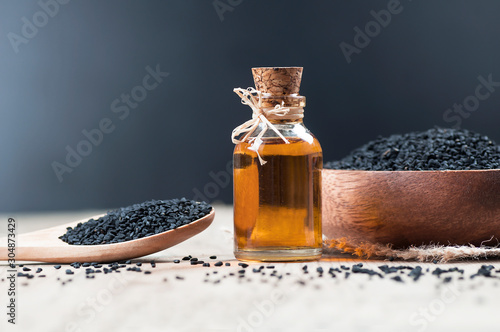 Obraz glass bottle of black cumin seeds essential oil , Nigella Sativa in spoon on wooden background. Organic herbal medicine for many diseases, black cumin - fototapety do salonu