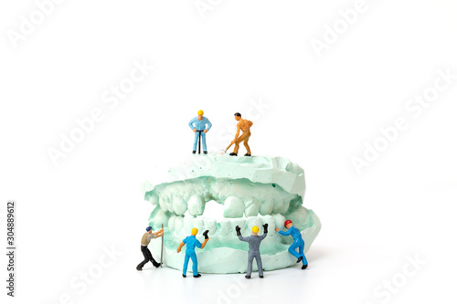 Photo Miniature people : Worker team repairing a tooth ,Healthcare and medical concept