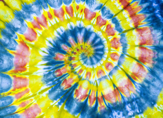 A bright yellow, red, and blue tye dye tunnel Fibonacci spiral pattern on cotton.