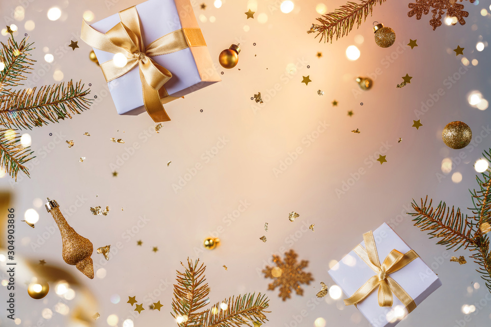 Fototapeta Merry Christmas and New Year background. Xmas holiday card made of flying decorations, gold fir branches, balls, snowflakes, sparkles, gift boxes, bokeh, light on golden background. Selective focus