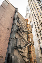 A View Looking Up A Black Painted Steel Fire Escape Adjacent To Weathered And Rusty Ductwork On A Multi Story Brick Building In An Urban Environment Surrounded By Highrise Buildings In Chicago.