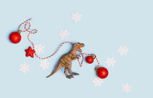 Dinosaur Plastic Toy With Christmas Red Balls, Snowflakes. Christmas And New Year Holiday Background. T-rex And Winter Decor On Blue Background. Funny Party. Winter Festive Creative Minimal Concept