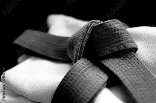 Photo Black judo, aikido or karate belt on white budo gi