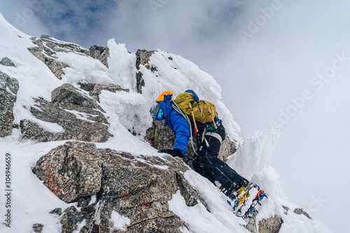 Leinwand Poster An alpinist climbing an alpine ridge in winter extreme conditions