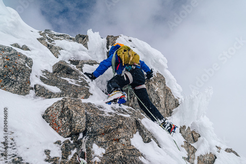 An alpinist climbing an alpine ridge in winter extreme conditions Fototapete