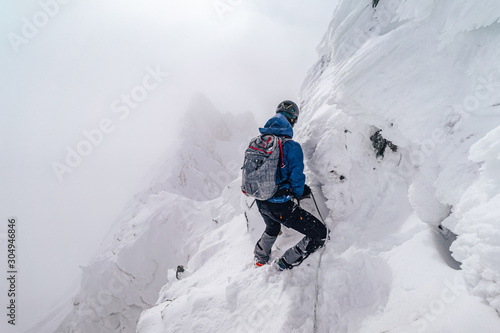 An alpinist climbing an alpine ridge in winter extreme conditions Canvas Print