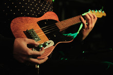 Performer Sets The Tone For Electric Ukulele In Green And Orange Lighting