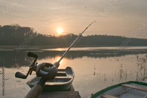 Fotomural Fishing boat in marina during sunset and fishing reel and rod