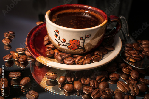 Wall Murals Cafe Small cup of coffee and coffee beans with reflection on shiny black background