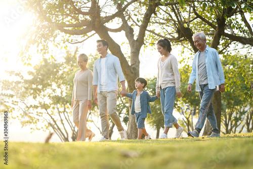 Obraz three generation asian family walking in park - fototapety do salonu