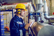 Leinwandbild Motiv Side view of dedicated factory worker standing next to boiler and holding tablet. Worker is dressed in protective uniform, having hardhat and antiphons.