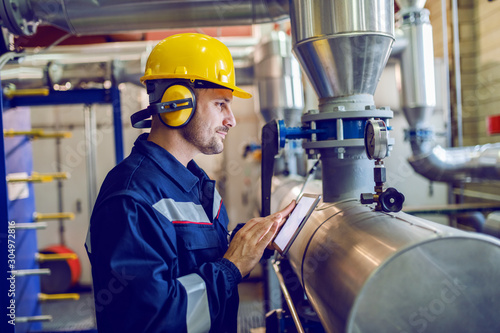 Obraz Side view of dedicated factory worker standing next to boiler and holding tablet. Worker is dressed in protective uniform, having hardhat and antiphons. - fototapety do salonu
