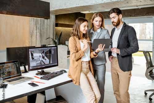 Small group of creative office employees working with digital tablet, standing together in the modern office of architectural firm