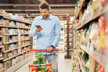 Young Adult Man Shopping In Supermarket And Using Smartphone