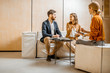 Young couple talking with a sales manager or real estate agent, sitting on the comfortable couch in the office