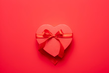 Female Hands Holding Red Heart Gift Box On Red Background. Valentine's Day Composition