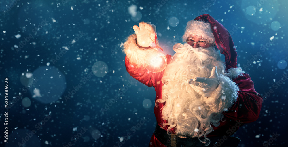 Fototapeta Happy Santa Claus holding glowing christmas ball over defocused blue background with copy space