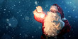 canvas print picture - Happy Santa Claus holding glowing christmas ball over defocused blue background with copy space