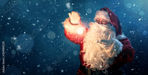 Happy Santa Claus holding glowing christmas ball over defocused blue background with copy space - 304989228
