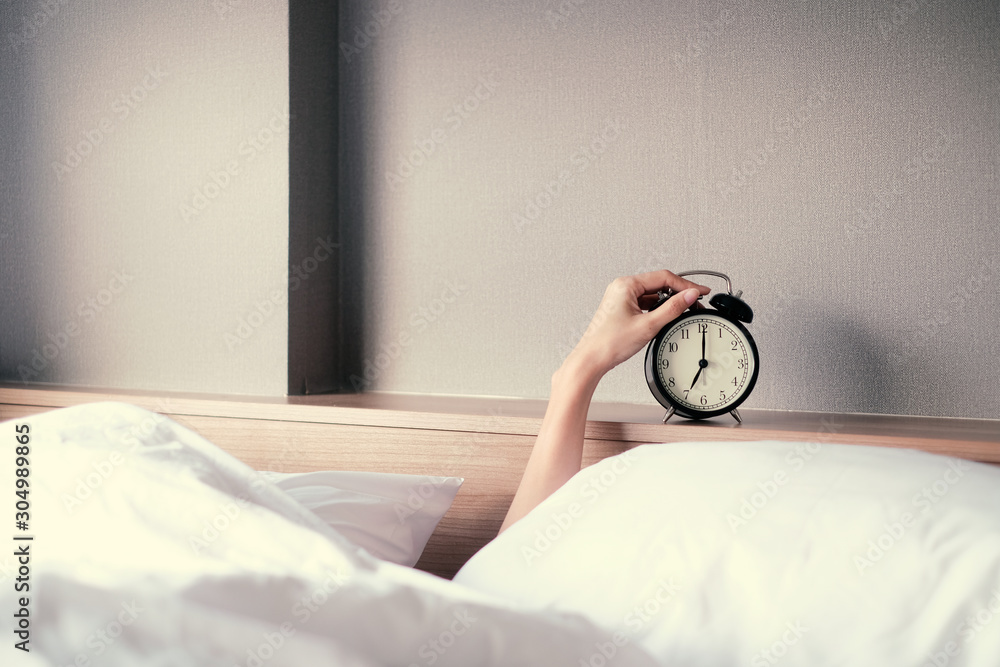 Fototapeta Woman sleep on the bed turns off the alarm clock wake up at the morning, Selective focus.