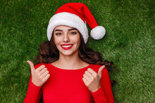 Smiling Woman In Santa Hat Gesturing Thumbs Up On Grass