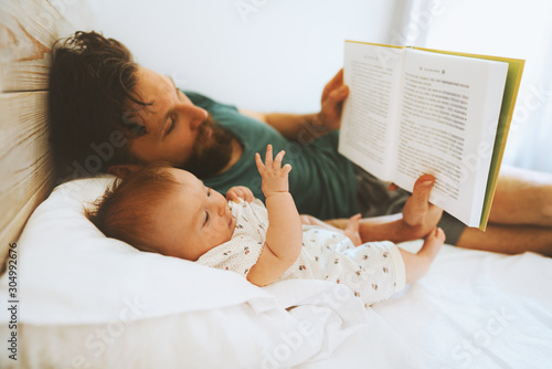 Family father and infant baby reading book fairytale laying on bed at home lifestyle dad and child daughter together parenthood childhood concept Fathers day holiday