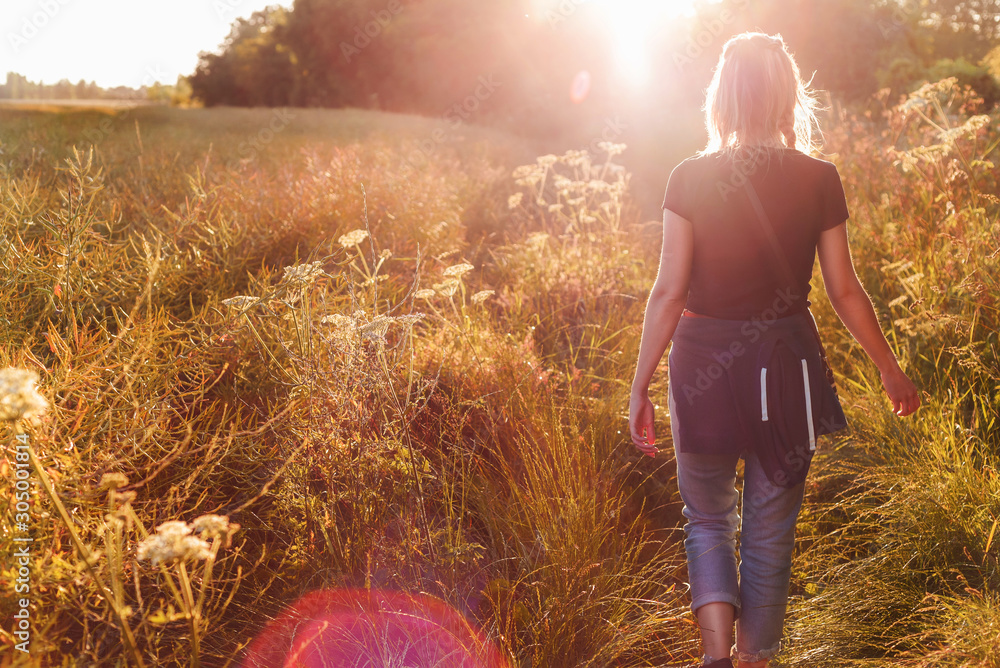 Fototapeta Beautiful young woman walking in field with sunrise