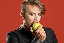 Portrait Of Young Transgender Woman Eating Apple On Color Background