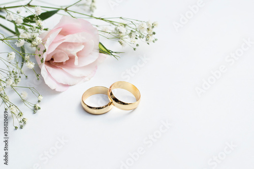 Fotomural Pink flowers and two golden wedding rings on white background.