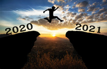 A Young Man Jump Between 2020 And 2021 Years Over The Sun And Through On The Gap Of Hill  Silhouette Evening Colorful Sky. Happy New Year 2021.