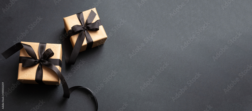 Fototapeta Gifts with black ribbon against black background, Black Friday concept.