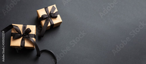 Gifts with black ribbon against black background, Black Friday concept. - 305032259