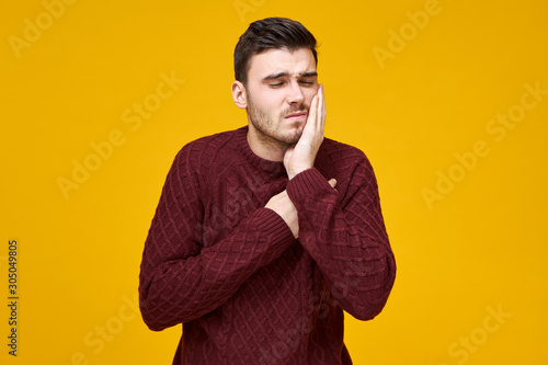 Fotografia Horizontal shot of happy frustrated young male in knitted jumper having problems