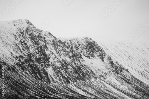 Valokuva cliff face on entry into the Lairig Ghru in the cairngorms national park during winter in November during a cold dark cloudy day